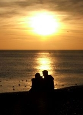 couple-sitting-on-beach-at-sunset-silhouette